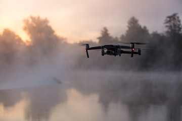 Drone copter with digital camera, river on background. Modern technology, UAV concept.