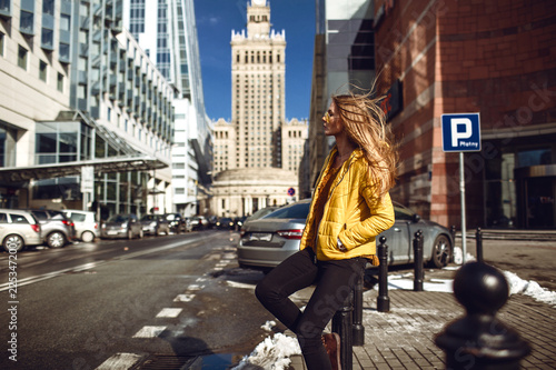 Leinwandbild Motiv A young European woman, traveling, with long blond hair, wearing a yellow jacket, yellow sunglasses walking down the city center street, street shooting. Even light.