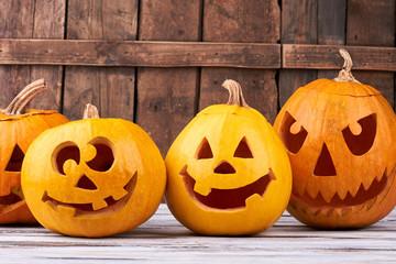 Halloween holiday pumpkins on wooden background. Orange autumn pumpkin Halloween holiday gourd jack o lantern faces.