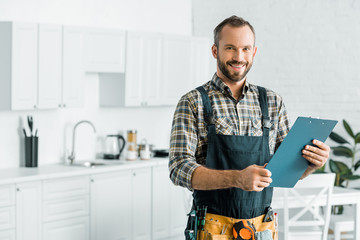 smiling handsome plumber holding clipboard and looking at camera in kitchen