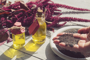 Bottles with amaranth oil, plants and amaranth seeds in the hand
