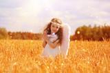 Девочка-ангел с крыльями, гуляющая по полю - 225373292
