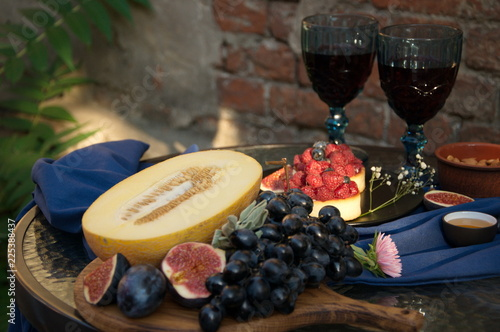 Fruit and wine on a glass table outdoor. - 225388437