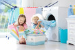 Leinwandbild Motiv Kids in laundry room with washing machine