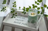 Green scented canle in jar on the a white, modern tray with fresh leaves in the background.