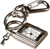 Silver keychain with little clock and key isolated on white