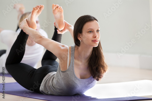 Leinwandbild Motiv Young sporty attractive woman practicing yoga, doing Dhanurasana exercise, Bow pose, working out, wearing sportswear, black pants, top, indoor full length, yoga studio. Well-being concept