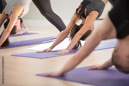 Leinwanddruck Bild Group of young sporty people practicing yoga lesson, doing Downward facing dog exercise, adho mukha svanasana pose, working out, indoor, students training in club, studio close up. Well being concept