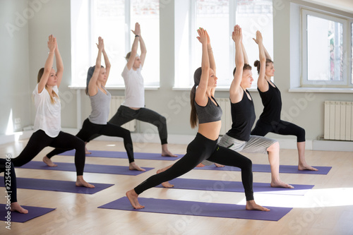 Leinwanddruck Bild Group of young sporty people practicing yoga lesson, doing Warrior one exercise, Virabhadrasana I pose, working out, indoor, students training in club, studio. Well-being concept