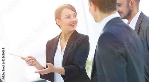 business woman showing a business team information on the flipchart