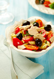 Pasta with tuna, cherry tomatoes, black olives, spices and fresh basil. Home made food. Concept for a tasty and healthy meal.  - 225453202