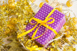 Violet elegant present with yellow ribbon on golden tinsesl and garland