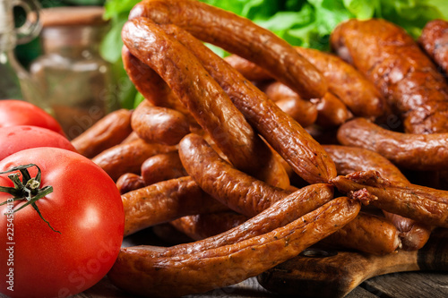 Assorted smoked sausages on a cutting board - 225458413