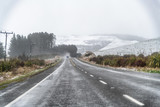 Road across countryside during a snow storm - 225464002