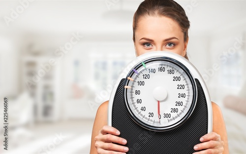 Young woman with scales isolated - 225466069