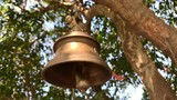 Close up of a Hindu Bell Swinging in slow motion with the crowd behind out of focus, on a sacred tree with red ribbons develop incredible India. Custom made wind bells are swinging with the breeze.  - 225468077
