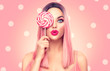 Beauty sexy model woman with trendy pink hairstyle and beautiful makeup holding lollipop candy, on pink polka dots background