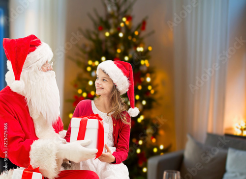 holidays, childhood and people concept - smiling girl and santa claus with gifts over christmas tree at home background