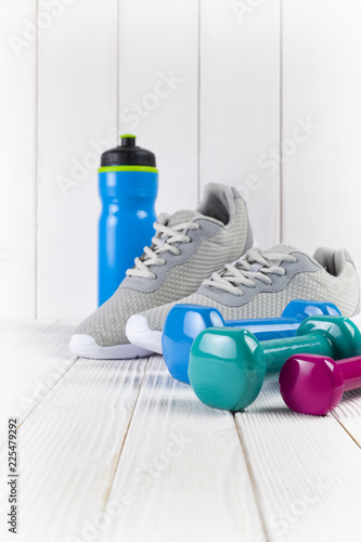 Poster Sneakers, water and dumbbell on wooden wall background as a sport and fitness symbols
