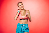 attractive smiling sportswoman plugging earphones and holding smartphone isolated on red