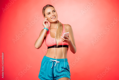 attractive smiling sportswoman plugging earphones and holding smartphone isolated on red - 225488869