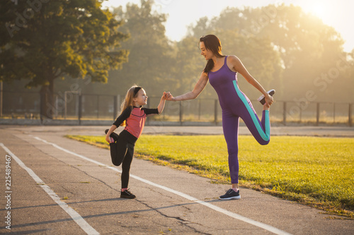 Mom and daughter on the morning sports training do a warm-up. Healthy lifestyle - 225489467