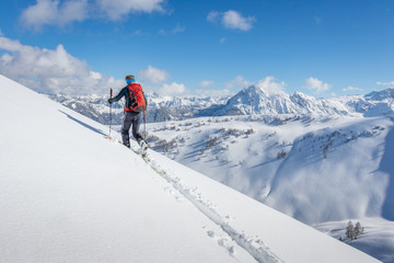Male ski tourer walking up a summit in the alps