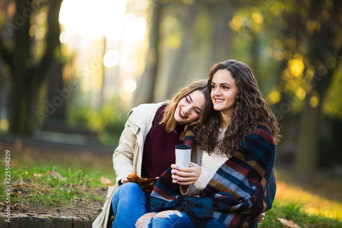 Two beautiful young women drinking coffee outdoors in the autmn