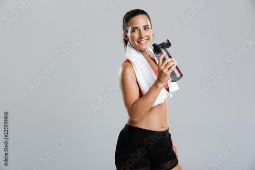 Leinwandbild Motiv Young sports woman posing isolated indoors drinking water with towel on neck.