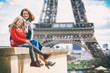 Mom and daughter on the background of the Eiffel Tower