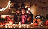 happy child girl in costumes of witch  in a dark house in halloween