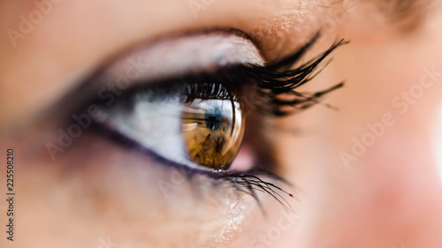 closeup of brown eye, reflection of sea and clouds, small depth of field - 225508210