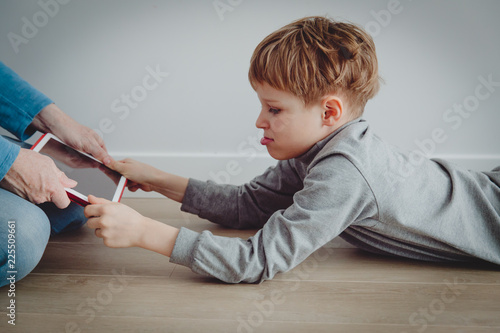 computer addiction- father taking touch pad from angry child - 225509661