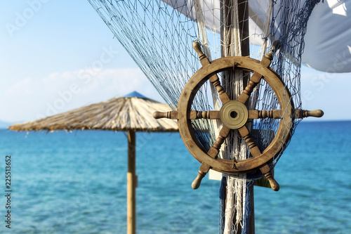 Wooden ship steering wheel and fishing net on the blue sea and sky background