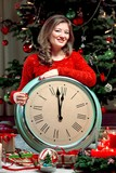Portrait of a young girl in red  sweater with alarm clock at Christmas lights background - 225516214