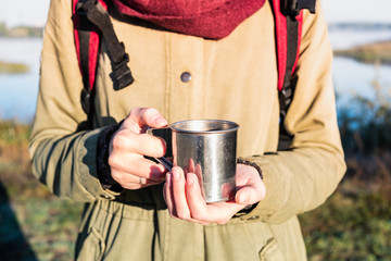 Woman hands holding a steaming cup of in beautiful nature environment. Enjoying a coffee in tourist metal cup at a hiking trip