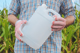 Farmer holding pesticide chemical jug in cornfield - 225518009