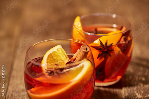 Leinwandbild Motiv close up view of mulled wine in glasses with orange pieces and spices on wooden tabletop