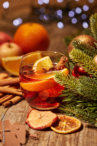 Leinwandbild Motiv close up view of tasty mulled wine drink with orange pieces and spices on wooden surface with bokeh lights on backdrop