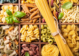 Spaghetti and assorted colorful italian pasta in wooden box. Healthy food background concept. Flat lay, top view.