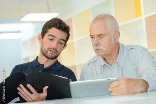 Foto Murales Men comparing information on tablet and in folder