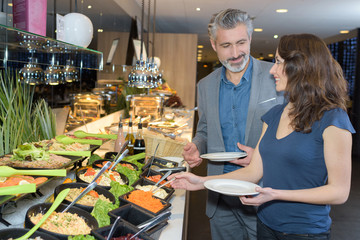 Man and woman serving themselves at buffet counter