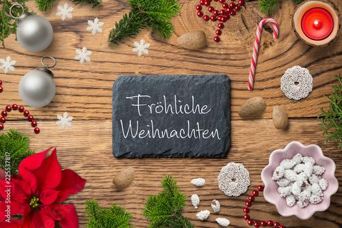 """Leinwandbild Motiv weihnachtliche Dekoration mit Nachricht """"Fröhliche Weihnachten"""" auf Schieferplatte und rustikalem Holzuntergrund"""