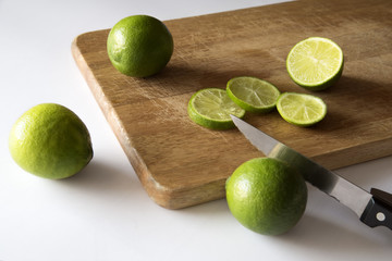 Limas y limones cortados en una tabla de madera
