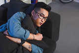 high angle view of young asian man in eyeglasses sleeping on sofa at home - 225542294