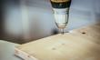 Handwerker bohrt Loch in Holzplatte, Bohrmaschine, Heimwerker