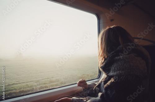 Girl in train looking through window