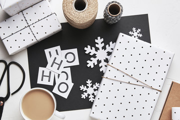 Flat lay Christmas composition with gift boxes and snowflakes in black and white colors. Gift wrapping. Top view