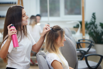 View from side of hairdresser fixing bouffant with hairspray in beauty salon