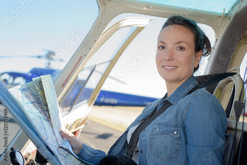 Fototapeta young woman helicopter pilot reading map
